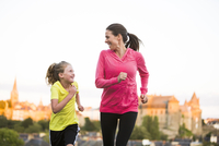 Caucasian mother and daughter jogging outdoors