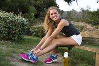 Caucasian woman tying shoe outdoors