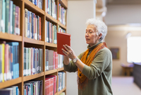 Older mixed race woman choosing book in library