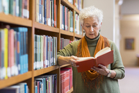 Older mixed race woman reading book in library