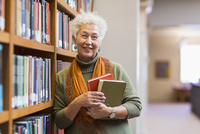 Older mixed race woman holding books in library