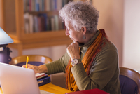 Older mixed race woman writing in library