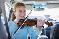 Caucasian girl playing violin in car