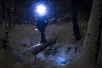 Caucasian hiker wearing headlamp balancing on forest log