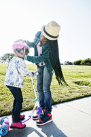 Black mother fastening helmet on daughter