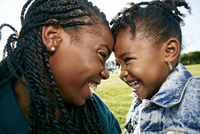 Black mother and daughter smiling outdoors