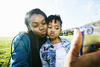 Black mother and daughter taking selfie outdoors