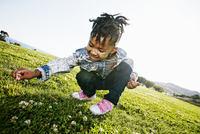 Black girl picking flowers in field