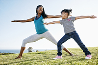 Black mother and daughter practicing yoga