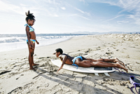 Black mother teaching daughter to surf on beach