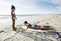 Black mother teaching daughter to surf on beach 11018066583| 写真素材・ストックフォト・画像・イラスト素材|アマナイメージズ