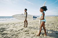 Black mother and daughter carrying surfboards on beach