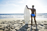 Black woman carrying surfboard on beach