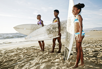 Three generations of Black women carrying surfboard on beach