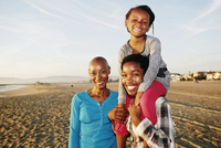 Three generations of Black women smiling on beach