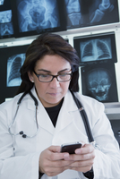 Hispanic doctor using cell phone in hospital