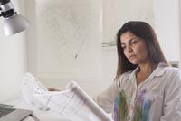Hispanic architect reading blueprints