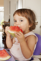 Hispanic baby girl eating watermelon