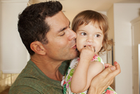 Hispanic father kissing baby daughter