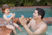 Hispanic father and baby daughter playing in pool