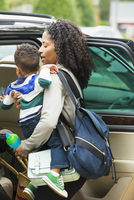 African American mother holding son near car