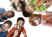 Children peering through magnifying glasses