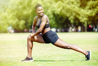 Black athlete stretching in park