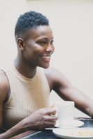Black woman drinking coffee in cafe