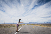 Hispanic man hitchhiking on remote road