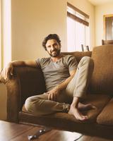 Hispanic man sitting on sofa
