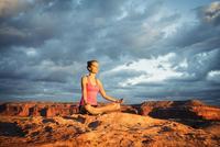 Hispanic woman practicing yoga on remote hilltop