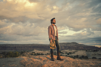 Hispanic man standing on remote hilltop