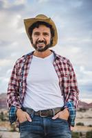 Hispanic man wearing cowboy hat outdoors