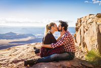 Hispanic couple kissing on remote hilltop