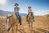 Hispanic couple riding horses on ranch