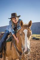 Hispanic woman riding horse on ranch