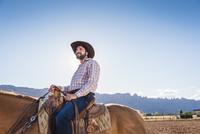 Hispanic man riding horse on ranch