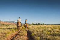 Hispanic couple riding horses on rural path