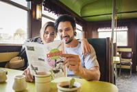 Hispanic couple reading menu in diner