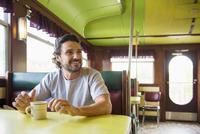 Hispanic man drinking coffee in diner