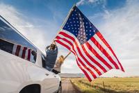 Hispanic couple waving American flag out car window