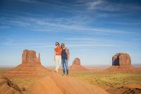 Hispanic couple standing on hilltop in remote desert