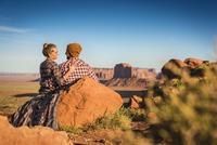 Hispanic couple hugging on hilltop in remote desert