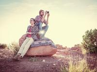 Hispanic couple sitting on boulder