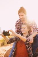 Hispanic couple taking selfie outdoors
