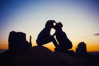 Silhouette of Hispanic couple kissing in desert landscape at sunset
