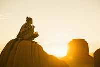 Hispanic woman sitting on rock formation in remote desert