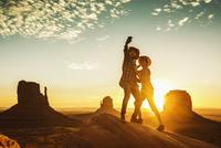Hispanic couple taking selfie on rock formation in remote desert