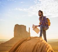 Hispanic man holding map in remote desert