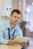 Caucasian man with Down Syndrome using digital tablet in hospital